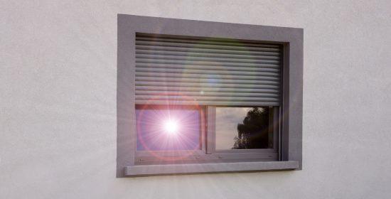 Hitzeschutz durch Rollladen und Fenster mit sich spiegelnde Sonne